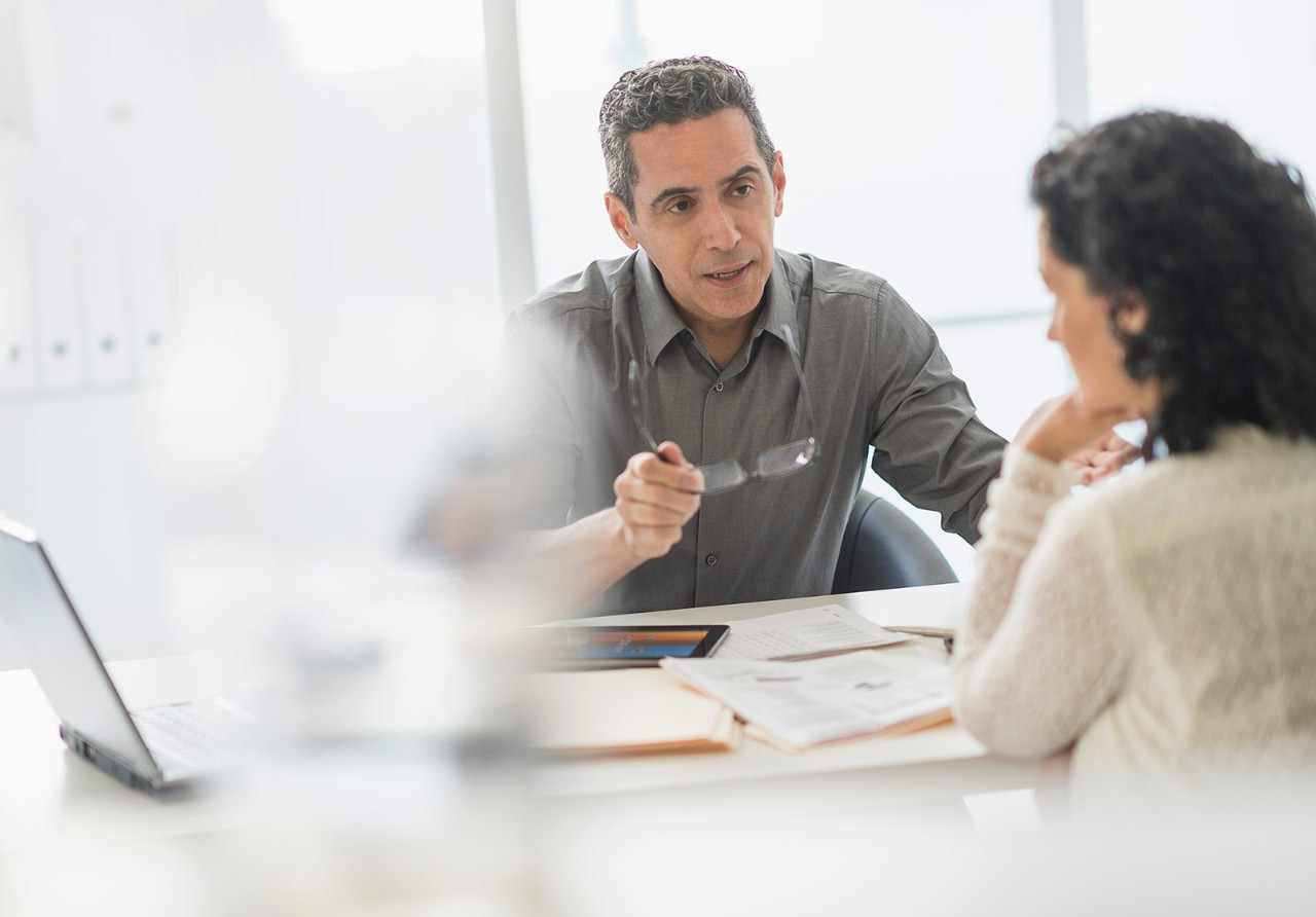 Businesspeople talking at desk in office, two people, meeting, conference
