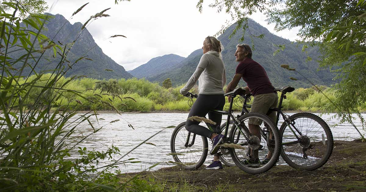 Bicyclist couple pause, look across river to hills